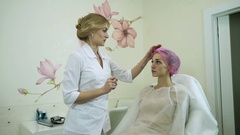 Cosmetologist making a mark on the face of the blonde girl for injection. HD Stock Footage