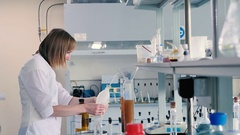 An employee fills a measuring beaker in the lab. Stock Footage