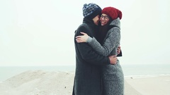 Young couple standing on the winter beach, rubbing his hands together Stock Footage