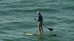 A woman sup stand-up paddleboard surfing at the beach, slow motion. Stock Footage