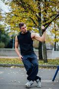 TRX training. Man Instructor at the park doing Excersise. Fitness workout Kuvituskuvat