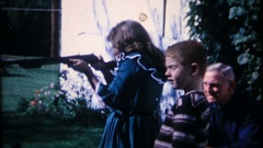 Children shoot BB gun while grandpa watches, 3867 vintage film home movie Stock Footage