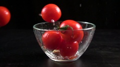 Falling cherry tomatoes in glass bowl, slow motion 250 fps Stock Footage