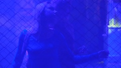 Beautiful ladies dancing temptingly behind metal chain fence in the nightclub Stock Footage