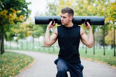 Male fitness doing exercise lunge with vipr, morning workout in the park Kuvituskuvat