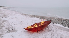 Red umbrella burns with a bright flame on the background of the sea and the Stock Footage