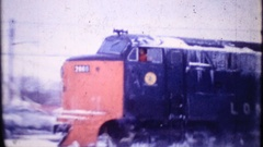 A train covered in ice and snow runs through town 3869 vintage home movie Stock Footage