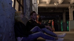 Blonde woman and man sitting near wall and talking, after-party, night life Stock Footage