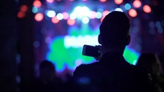 Active man shaking hand and filming live show at night club, dancing people Stock Footage