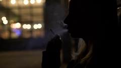 Silhouette of sad woman smoking outside night club, bad habits, depression Stock Footage