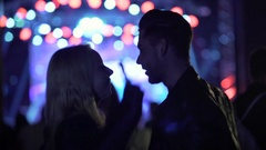 Smiling couple dancing and talking at concert, people enjoying music at club Stock Footage