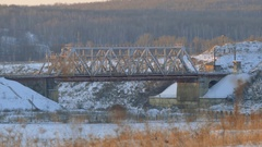 Working locomotive passes through a railway bridge. Winter landscape Stock Footage