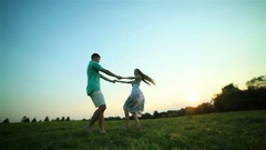 Happy couple in love spin around holding hands low angle POV Stock Footage