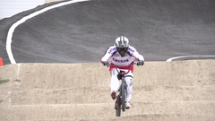 A young man bmx rider riding on a dirt track, super slow motion. Stock Footage