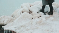 Icy stone ridge. Young couple standing on the bank of the winter sea. close-up Stock Footage