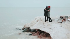 Icy stone ridge. Young couple standing on the bank of the winter sea Stock Footage