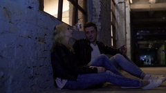 Young couple sitting on floor, talking about problems and hugging, support Stock Footage