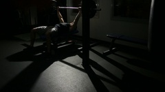 Athlete man does bench press from chest exercise in gym hall Stock Footage