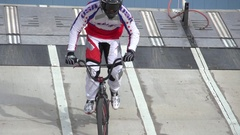 A young man bmx rider riding on a dirt track , slow motion. Stock Footage