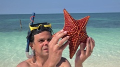 Snorkeler considering big starfish (Oreaster reticulatus) on the shore. Stock Footage