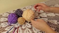 Girl unwinds a skein of yarn for knitting crochet. Crochet tablecloth handmade. Stock Footage