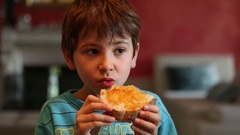 Young boy eating bread with marmalade Kid eating breakfast in the morning Stock Footage