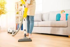 Woman use vacuum cleaner to cleaning Stock Photos