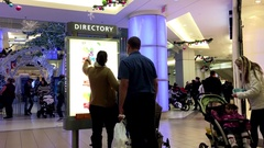 Couple checking store position in front of directory sign inside shopping mall Stock Footage