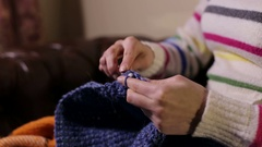 A woman crocheting on the couch. Female's hands knitting woolen threads. Stock Footage