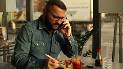 Young man talking on cellphone, eating sushi bar restaurant Stock Footage