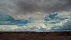 Time lapse storm clouds travel over a desert plain. HD stock footage. Stock Footage