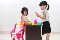 Asian Chinese little sisters pretending customer and cashier with trolley Kuvituskuvat