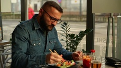 Man having toothache while eating in restaurant Stock Footage