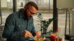 Hungry man eating sushi and looking funny in the restaurant Stock Footage