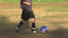 Boys ages 6 to 8 playing in a youth soccer league game, super slow motion. Stock Footage