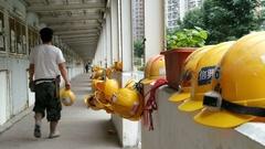 HONG KONG  Tseung Kwan O yellow hard hats construction site Stock Footage