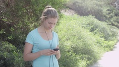 A young woman runner putting on earbuds before going on a run, slow motion. Stock Footage