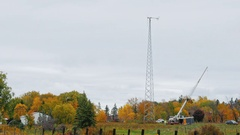 Group workers preparing to repair a wind turbine in a small farm. Crane boom Stock Footage
