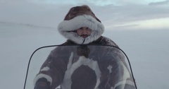 A portrait of a tired traveler with a hood fur on a snowmobile. YAMAL 2016 Stock Footage