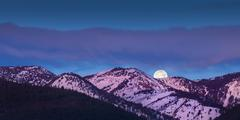 Moon rise over mountains with alpen glow pink light Stock Photos