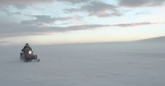 A traveler dressed in traditional Yamal clothes driving a snowmobile in arctic Stock Footage