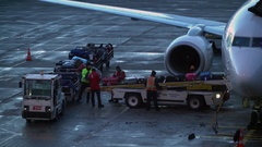 Airport employees load and unload baggage on conveyor to airplane Stock Footage