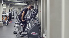 Young Muscular Man Exercising on climbing simulator Machine. in the background Stock Footage