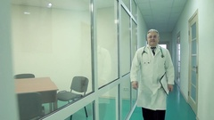 The doctor walks down the hospital corridor in a white robe and a folder in his Stock Footage