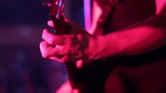 Band guitarist singing on stage under the spotlight at a concert durin Stock Footage