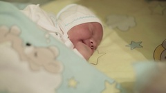 Close up. Newborn baby lying in bed and yawns. Stock Footage