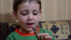 Boy biting a bar of chocolate and is very happy Stock Footage