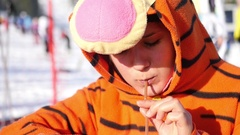 Beautiful girl dressed as tigers drink mulled wine through a straw, the outdoor Stock Footage