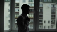 Man dressing silhouetted near window. Male hands hurrying to button shirt Stock Footage