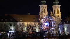 Amusement park built in front of a church that towers illuminated by s Stock Footage